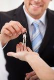 Fastighetsmäklare som ger hustangenter till mannen Royaltyfria Bilder