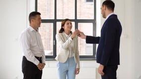 Fastighetsmäklare som ger tangent till kunder på det nya kontoret arkivfilmer