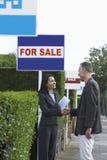 Fastighetsmäklare som skakar händer med mannen bredvid till salu tecken Arkivfoto