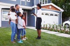 Fastighetsmäklare som visar en familj ett hus arkivbild