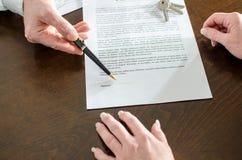 Fastighetsmäklare som visar häftestället av ett avtal Arkivbilder