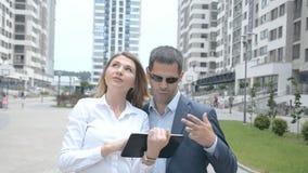 Fastighetsmäklareflickan visar ett modernt bostads- komplex till en potentiell köpare lager videofilmer