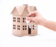 Fastighetsmäklarehand över egenskap eller nya hem- tangenter till en kund på vit Royaltyfri Foto