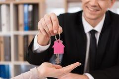 Fastighetsmäklaren ger kvinnatangenter med keychain i form av huset till det nya huset Förvärv av hus royaltyfria bilder