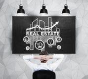Fastighetsmäklaren sitter framme av den svart tavlan med skissa av tillfällena av fastighetmarknaden royaltyfri fotografi