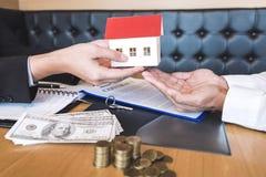 Fastighetsmäklaren som överför husmodellen till klienten, når han har undertecknat överenskommelseavtalsfastigheten med godkänt,  arkivfoto