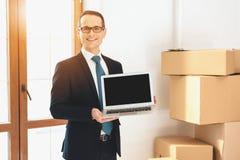 Fastighetsmäklaren som framlägger bärbara datorn i ny lägenhet med kartonger, near dörrar royaltyfria foton