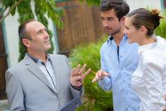 Fastighetsmäklaren som talar till barn, kopplar ihop den främsta egenskapen royaltyfri bild