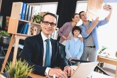 Fastighetsmäklaresammanträde på skrivbordet i regeringsställning Fastighetsmäklaren arbetar på bärbara datorn med familjen i bakg royaltyfri fotografi