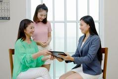 Fastighetsmäklareslut ett avtal Asiatisk familj som köper det nya hemmet, busi Arkivbild