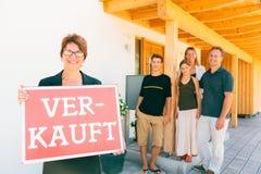 Fastighetsmäklare med den tyska familjen som säljer deras hus Royaltyfri Foto