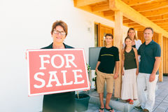 Fastighetsmäklare med familjen som säljer deras hus Royaltyfri Fotografi