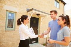 Fastighetsmäklare som skakar händer med nya egendomsägare Arkivfoto