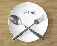 Fasting. Paper and fork with spoon symbol on white plate Stock Image