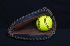 Fastpitch垒球有黄色球的俘获器露指手套 免版税图库摄影
