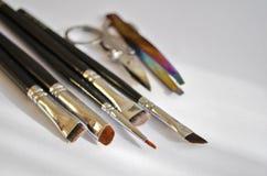 Fastställd hjälpmedelsminkkonstnär en uppsättning av olik borstar för makeupkonstnär och sax och pincett i solsken royaltyfri bild