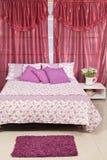 Fastställd säng i rummet med gardiner Arkivbild