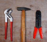 Fastställda handhjälpmedel med hammaren, klor, skruvmejsel, på träbakgrund fotografering för bildbyråer