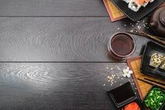 Fastställda sashimi- och sushirullar för sushi och liten vit blomma på mörk bakgrund Arkivfoton