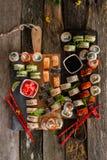 Fastställt matfoto för sushi Rolls tjänade som på brunt trä och kritiserar plattan Övre och bästa sikt för slut av sushi arkivfoton