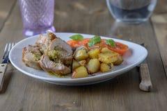 Faszerująca wieprzowina polędwicowa z pomidorami i basilem na stronie na ol Fotografia Stock