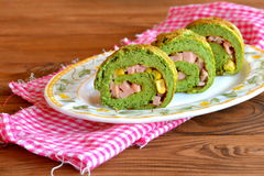 Faszerująca zielona omelette rolka z szpinakiem na talerzu na drewnianym stole Omelette rolki faszerowali z serem, kiełbasą i kuk Obraz Stock