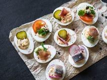 Faszerujący jajka z różnorodną polewą Prosciutto, śledź, kiszony ogórek, kiełbasa, rzodkiew, pomidor, kapary i sezam na gotowanym obraz royalty free