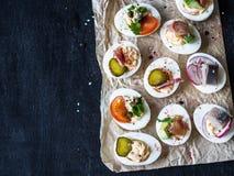 Faszerujący jajka z różnorodną polewą Prosciutto, śledź, kiszony ogórek, kiełbasa, rzodkiew, pomidor, kapary i sezam na gotowanym zdjęcia royalty free