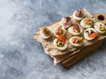 Faszerujący jajka z różnorodną polewą Prosciutto, śledź, kiszony ogórek, kiełbasa, rzodkiew, pomidor, kapary i sezam na gotowanym zdjęcie royalty free