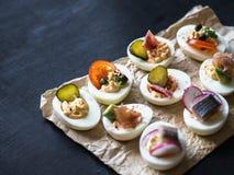 Faszerujący jajka z różnorodną polewą Prosciutto, śledź, kiszony ogórek, kiełbasa, rzodkiew, pomidor, kapary i sezam na gotowanym obrazy royalty free