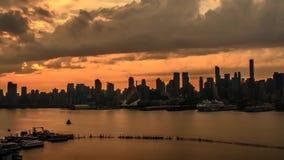 Faszinierendes stabiles Zeitspannepanorama der grauen Regenwolke, die wenn orange Sonnenunterganghimmel über New- York Cityskylin stock video footage