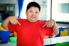 Fat Asian child boy has a smiling face, hands pointing at the chest stock photo