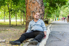 A fat Asian guy sleeping under the tree beside the street. Stock Photo