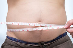 Fat asian man use waist measure for his belly Royalty Free Stock Photo