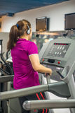 Fat Asian woman is exercising hard on a treadmill Royalty Free Stock Images