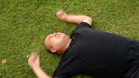 A fat bald head Asian Thai man is acting wriggling like a spoil child having seizures with angry aggressive face or having mental stock footage