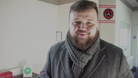 Fat bearded guy says something to the camera before he goes to the gym to burn calories and lose weight. A man will do stock footage