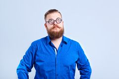 A fat, bearded man clever with glasses with a clever stupid expr. A fat, bearded man clever with glasses on a gray background with a clever stupid expression of royalty free stock images