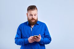 A fat, bearded man looks at the phone  with a surprised expressi Royalty Free Stock Images