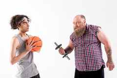 Fat bearded man pestering to slim boy. Angry male fatso is threatening to weak guy while holding weight. Victim is holding ball and looking at hipster with dread Stock Photography