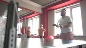 Fat caucasian bearded man playing table tennis in a modern gym, dumping excess weight, slow motion stock footage