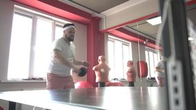 Fat caucasian bearded man playing table tennis in a modern gym, dumping excess weight, slow motion, friendship stock video