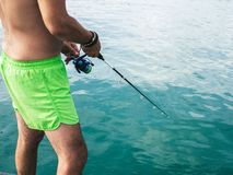 Fat belly man fishing in the sea stock image