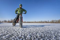 Fat bike cyclist on a frozen lake in winter Royalty Free Stock Image