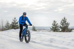 Fat bike. Fat tire bike. A young man riding fat bicycle in the winter. A young man riding fat bicycle in the winter. winter biking. Fatbike. Fat tire bike royalty free stock photography
