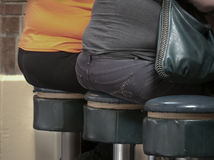 Fat bottom ladies. Sitting on round bar stools Royalty Free Stock Photos