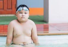 Fat boy bored to swimming lesson Stock Photo