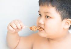 Fat boy eat grilled pork Royalty Free Stock Photos