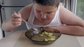 Fat boy eating soup. improper diet problems with excessive weight in children. concept of sedentary lifestyle. stock video
