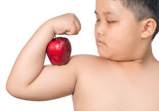 Fat boy flexes him muscle while showing off the apple that made. Her strong and healthy isolated Royalty Free Stock Photography